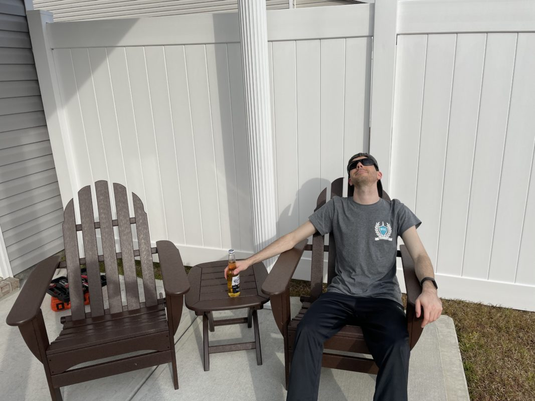 Customer relaxing in adirondack chair set from Plastic Lumber Yard
