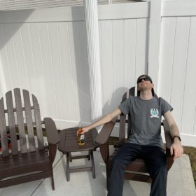 Customer relaxing in adirondack chair set from Plastic Lumber Yard